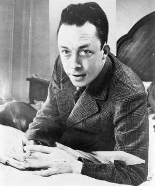 499px-Albert_Camus,_gagnant_de_prix_Nobel,_portrait_en_buste,_posé_au_bureau,_faisant_face_à_gauche,_cigarette_de_tabagisme